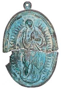 太陽を背に頭上に7星をめぐらし、弦月(げんげつ)を踏んで立つ青銅製の「無原罪の聖母」のメダリオンです。  昭和7年大村高校新築工事の際、島原の乱後の寛永16年(1639年)の銘が刻まれた大村藩家老宇田家の墓から出土したもので、スペイン王カルロス一世の代(1516年~1556年)にマドリッドの王立造幣局で製造されたものです。  縦11.4㎝、横7.4㎝の楕円形で、掘り出す時二つに割れたものと思われ、現在史料館にあります。